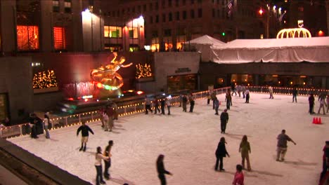 The-Camera-Shows-Skaters-At-Night-On-The-Rockefeller-Center-Ice-Rink-And-Then-Pans-Up-The-Ge-Building