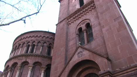 The-Camera-Pans-Up-For-A-Wormseye-View-Of-The-Facade-Of-A-Red-Stone-Church-To-Focus-On-Ornamentation