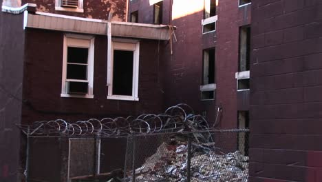 A-Cyclone-Fence-And-Barbedwire-Should-Prevent-Unwanted-Visitors-From-Accessing-An-Airconditioner-That-Still-Sits-In-A-Window-Of-An-Abandoned-Building