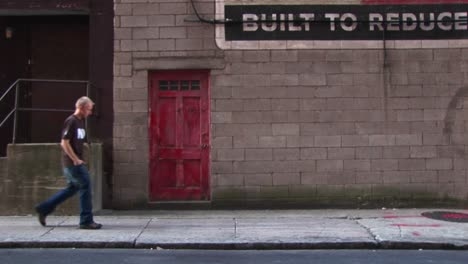 A-Young-Man-Walks-By-Old-Building-With-A-Red-Door