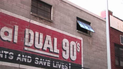The-Camera-Zooms-In-On-An-Open-Window-Past-Advertising-On-An-Old-Building