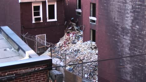 In-This-Innerscene-The-Camera-Pans-Up-And-Over-A-Rooftop-To-View-Trash-Piling-Up-Around-An-Old-Apartment-Building