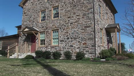 The-Camera-Pans-Up-The-Exterior-Of-A-Threestory-Fieldstone-House-With-Two-Entrances