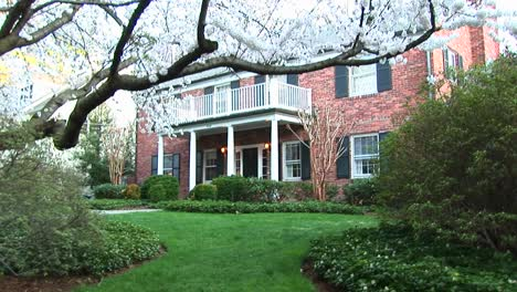 A-Medium-View-Of-Red-Brick-Suburban-Home-In-Early-Spring-With-Flowering-Trees