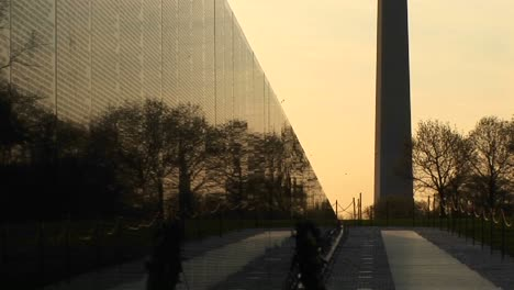 With-A-Golden-Sky-Backdrop-The-Washington-Monument-Is-Seen-In-Silhouette-Next-To-The-Vietnam-Memorial-Wall