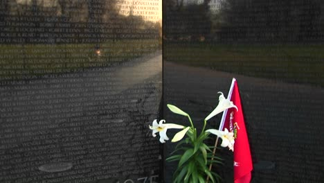 A-Pot-Of-White-Lilies-Holding-A-Red-Flag-Stands-At-The-Foot-Of-The-Vietnam-Veterans-Memorial-Wall-In-Washington-Dc-Whose-Granite-Surface-Reflects-The-Surrounding-Landscape
