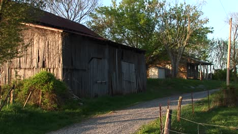 Mediumshot-Of-An-Old-Barn-Next-To-A-Dirt-Road-With-House-In-The-Background