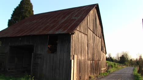 Sunlight-Rejuvenates-Aged-Timbers-Of-An-Old-Abandoned-Barn-Sitting-On-The-Edge-Of-A-Onelane-Road