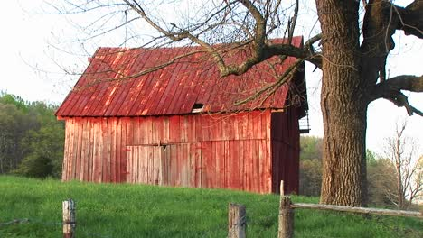 Faded-Red-Roof-And-Siding-Of-An-Old-Barn-Reflects-The-Passing-Of-The-Family-Farm-And-An-Entire-Era