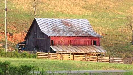 Cars-Pass-By-An-Old-Abandoned-Farm-Shed-And-Leanto-That-Recalls-The-Passing-Of-The-Family-Farm-And-An-Entire-Era-In-American-History