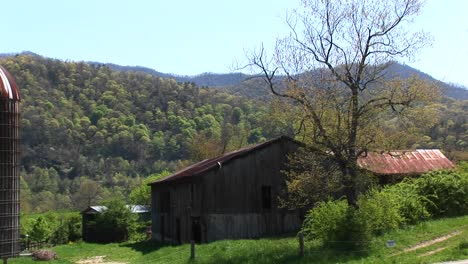 A-Country-House-And-Barn-Sit-Surrounded-By-Beautiful-Mountain-Scenery