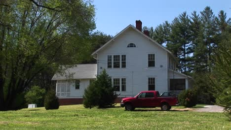 A-Newer-Model-Red-Pickup-Sits-Parked-In-Front-Of-A-Quaint-White-Farmhouse