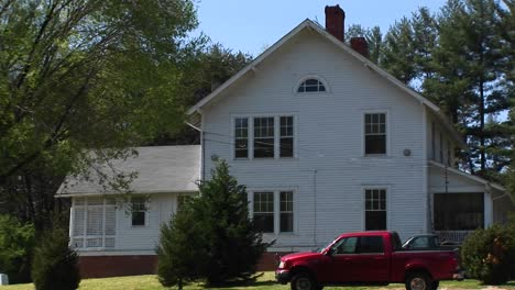 Camera-Zooms-In-To-A-Window-On-The-Second-Story-Of-A-White-Farmhouse