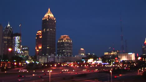 Skyscrapers-Make-Up-The-Background-For-An-Evening-Panning-Shot-Of-Traffic-Flowing-Along-On-An-Atlanta-Freeway