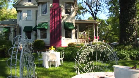 Tables-And-Chairs-Furnish-The-Yard-Of-A-Victorian-Home-Flanked-By-A-Bright-Red-Chimney