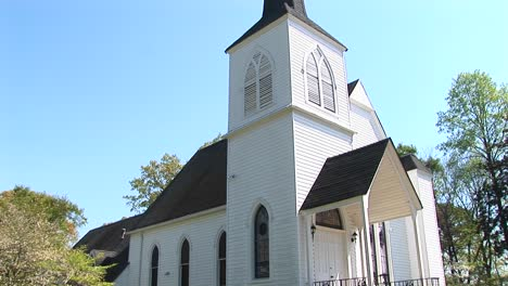 An-Old-Rural-Church-Stands-Tall-Over-The-Country-Lane-In-Front-Of-It