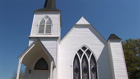 The-White-Clapboard-Exterior-Of-An-Old-Country-Church-Is-Set-Against-A-Blue-Sky-In-This-Panning-Shot