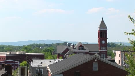 The-Camera-Pansright-Across-The-Roofline-Of-A-Small-Town-To-Highlight-An-Old-Clock-Tower