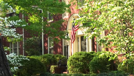 An-American-Flag-Seen-Through-The-Trees-Hangs-Proudly-Beside-A-Home-S-Doorway