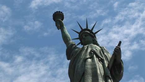 The-Statue-Of-Liberty-Proudly-Stands-Silhouetted-Against-A-Blue-Sky