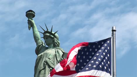 The-American-Flag-Waves-In-The-Foreground-With-The-Statue-Of-Liberty-Standing-Proudly-Behind