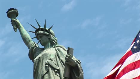 The-Camera-Pansleft-Across-A-Rippling-American-Flag-Revealing-The-Statue-Of-Liberty-In-The-Background