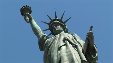 The-Camera-Looks-Up-At-A-Towering-Statue-Of-Liberty-Set-Against-A-Blue-Sky