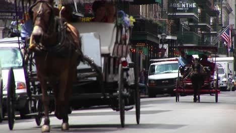 Mule-Buggies-Follow-Each-Other-Down-A-Crowded-Street-In-New-Orleans