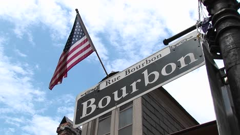 An-American-Flag-Flies-Above-A-Street-Sign-Identifying-New-Orleans-S-Famed-Bourbon-Street