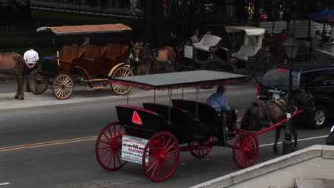 Muledrawn-Buggies-Wait-For-Tourists-While-Another-Buggy-Makes-Its-Way-Down-A-Crowded-Street-In-New-Orleans