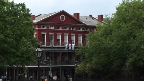 A-Mediumshot-Of-Repairmen-Standing-On-The-Balcony-Of-An-Old-Brick-Building-Doing-Repairs