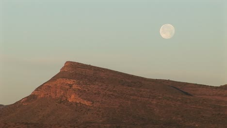 Mediumshot-Of-The-Moon-Hovering-Over-A-Rocky-Landscape