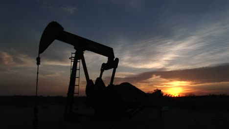 Medium-Shot-Of-A-Silhouetted-Oil-Pump-Turning-In-The-New-Mexico-Desert-Pumping-Petroleum