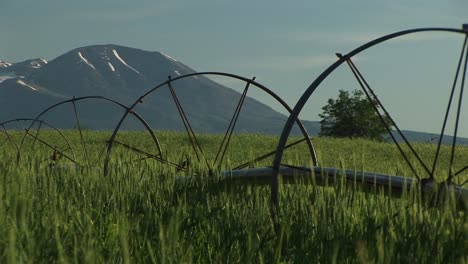 Medium-Shot-Of-Irrigation-Sprinklers-On-Utah-Farmland-And-The-La-Sal-Mountains-In-The-Background