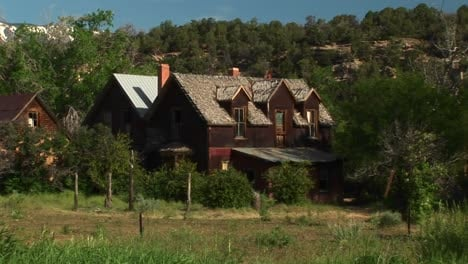 Medium-Shot-Of-An-Abandoned-Ranch-House-Sitting-In-A-Grove-Of-Trees