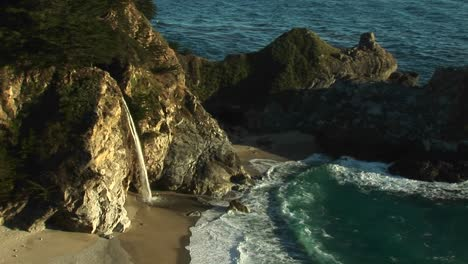 Birdseye-Shot-Of-A-Waterfall-Crashing-Down-Into-A-Secluded-Pool-Of-The-California-Pacific-Ocean