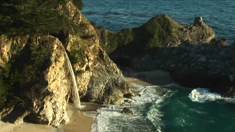 Birdseye-Shot-Of-A-Waterfall-Crashing-Down-Into-A-Secluded-Pool-Of-The-California-Pacific-Ocean-1