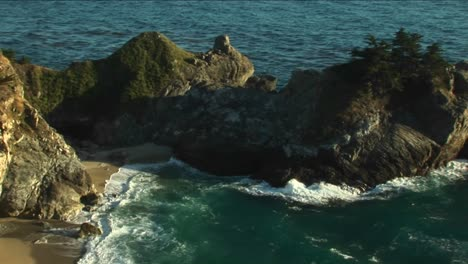 Panleft-Shot-Of-A-Rocky-California-Coast-And-A-Waterfall-Crashing-Down-Into-A-Secluded-Pool-At-Julia-Pfeiffer-Burns-State-Park