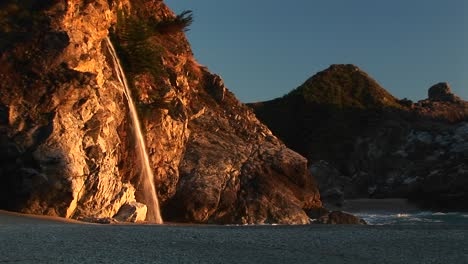 Mediumshot-Of-A-Waterfall-Crashing-Down-Onto-A-Secluded-Beach-In-The-Julia-Pfeiffer-Burns-State-Park-Along-The-California-Pacific-Ocean