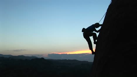 Longshot-Of-A-Rock-Climber-Scaling-A-Cliff-Silhouetted-Against-A-Goldenhoursky