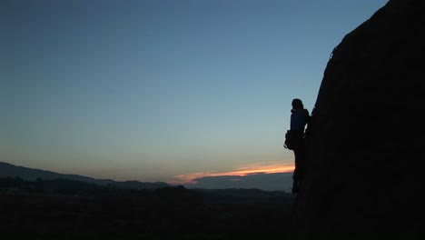 Longshot-Of-A-Rock-Climber-Scaling-A-Cliff-Silhouetted-Against-A-Goldenhoursky-1