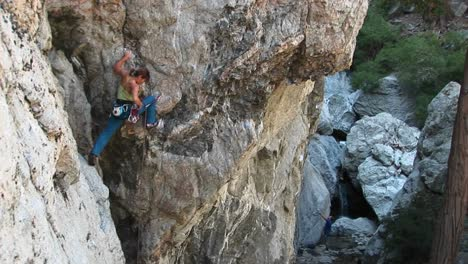Longshot-Of-A-Rock-Climber-Rearranging-Her-Carabineers-To-Climb-A-Cliff-Wall
