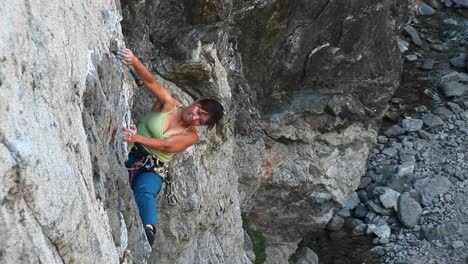Bird-Seye-Shot-Of-A-Rock-Climber-Struggling-To-Pull-Herself-Up-A-Cliff-Wall