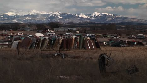 Mediumshot-Of-A-Car-Junkyard-In-Front-Of-The-Scenic-Rocky-Mountains