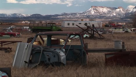 Medium-Shot-Of-Rusting-Cars-In-Front-Of-The-Rocky-Mountains