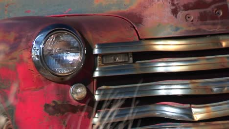 Closeup-Of-Dented-And-Rusting-Abandoned-Pickup-Truck-Showing-Front-Passenger-Side-Headlight-Grill-And-Hood