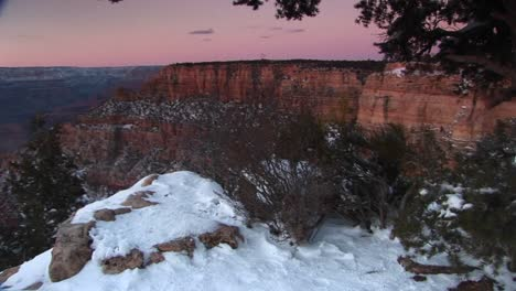 Wide-Shot-Of-Grand-Canyon-National-Park-With-Foreground-Of-Cliffs-Edge-And-Snowcovered-Rocks-Shrubs-And-Trees