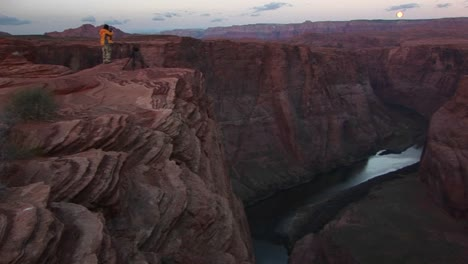Wide-Shot-Of-A-Photographer-Standing-On-Cliff-And-Photographing-The-Canyons-Of-The-Colorado-River-As-It-Weaves-Through-Tight-Sandstone-Canyons-Under-A-Full-Moon-Rising