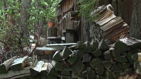 Medium-Shot-Of-Rural-Cabin-With-Wood-Pile-In-The-Sierra-Nevada-Mountains