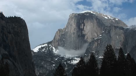 Medium-Wide-Shot-Of-Yosemite-S-Half-Dome-Hosting-Clouds-And-Winter-Snow